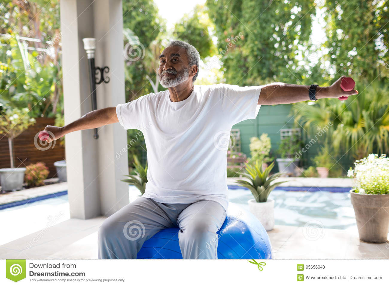 Senior man with arms outstretched lifting dumbbell while exercising