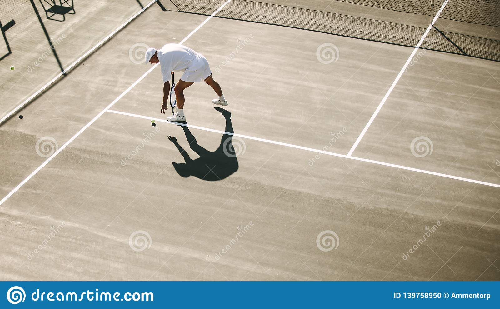 Senior man bending down to pick a tennis ball during a game of t stock photo