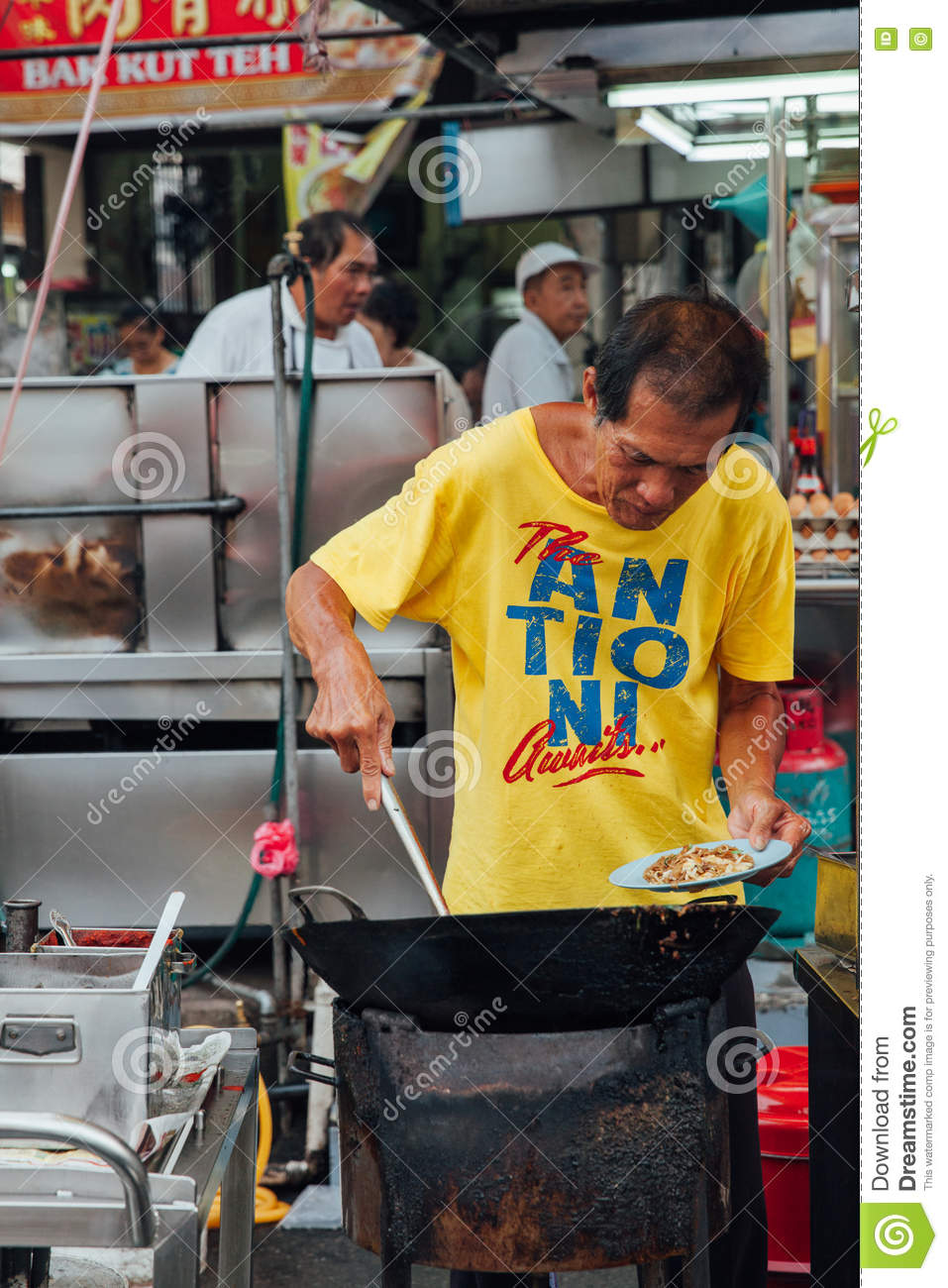 George Town, Malaysia - March 22, 2016: Senior man cooks kway teow noodles  in asian wok at the Kimberly Street Food Night Market on March 22, 2016 in  George ...