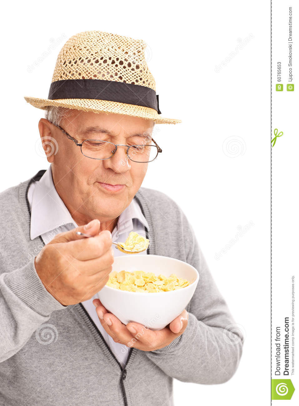 Senior man eating cereal with a metal spoon