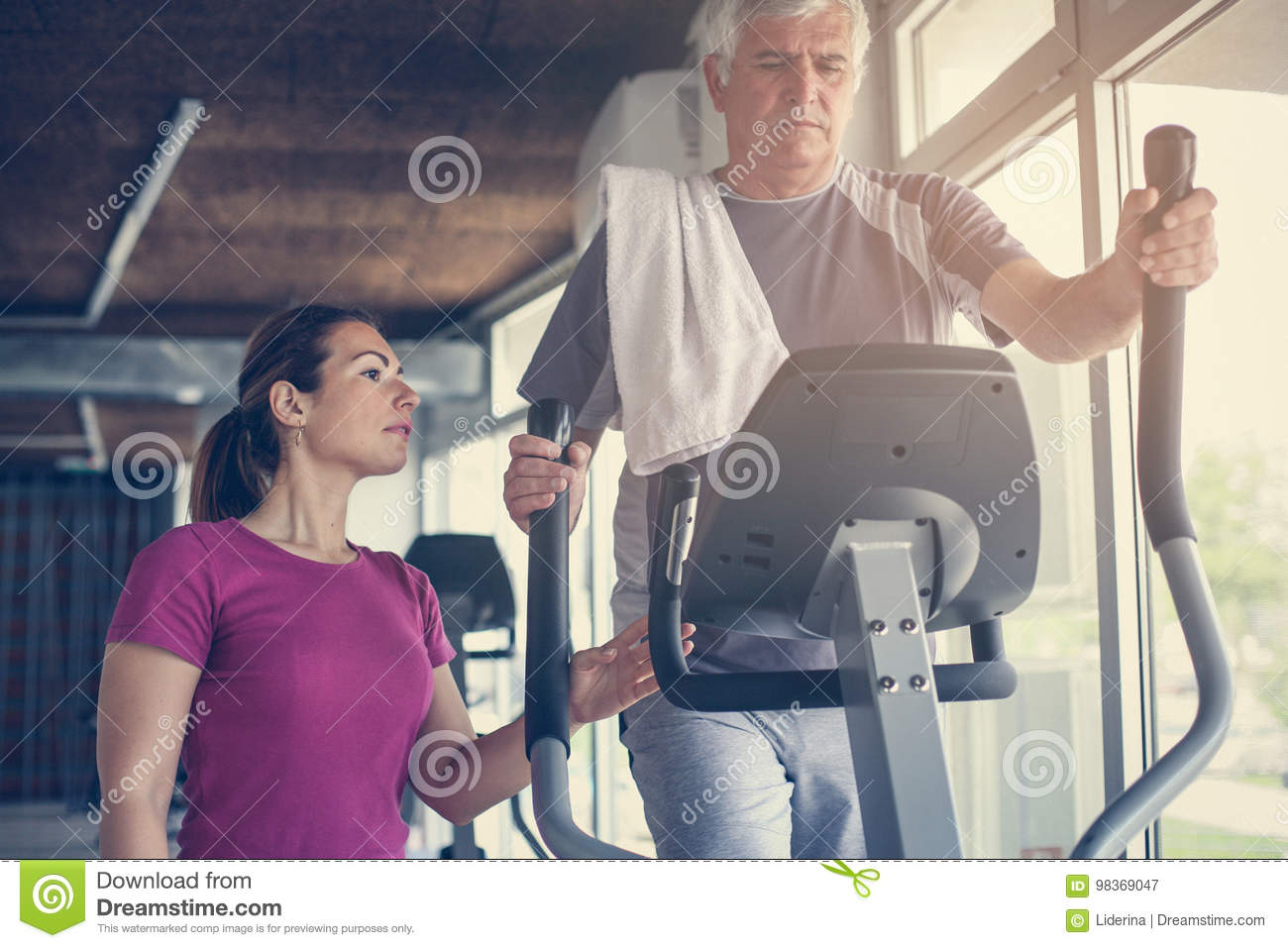Senior man exercising on stationary bikes.