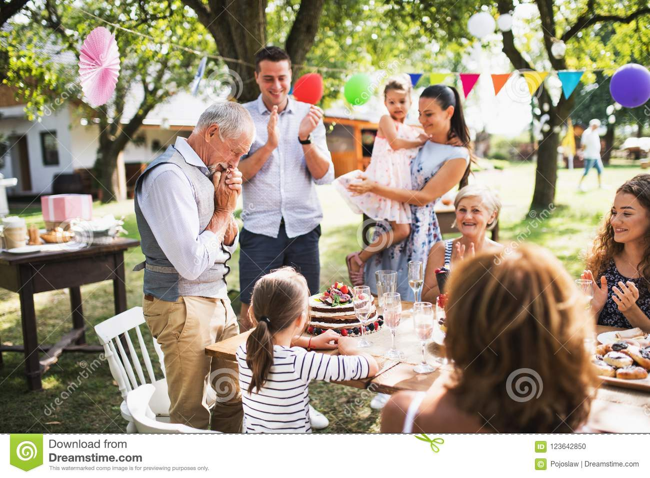 A senior man with an extended family looking at the birthday cake, crying.