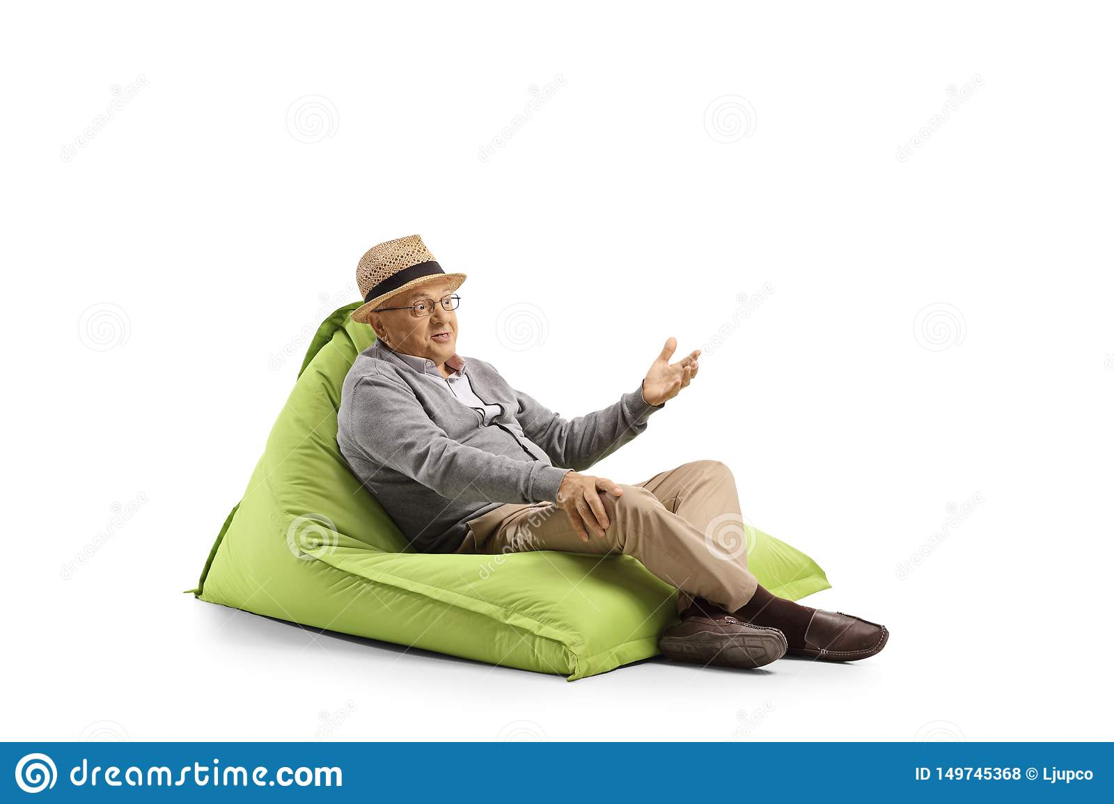 Senior man with face expression resting on a bean-bag armchair and gesturing with hand