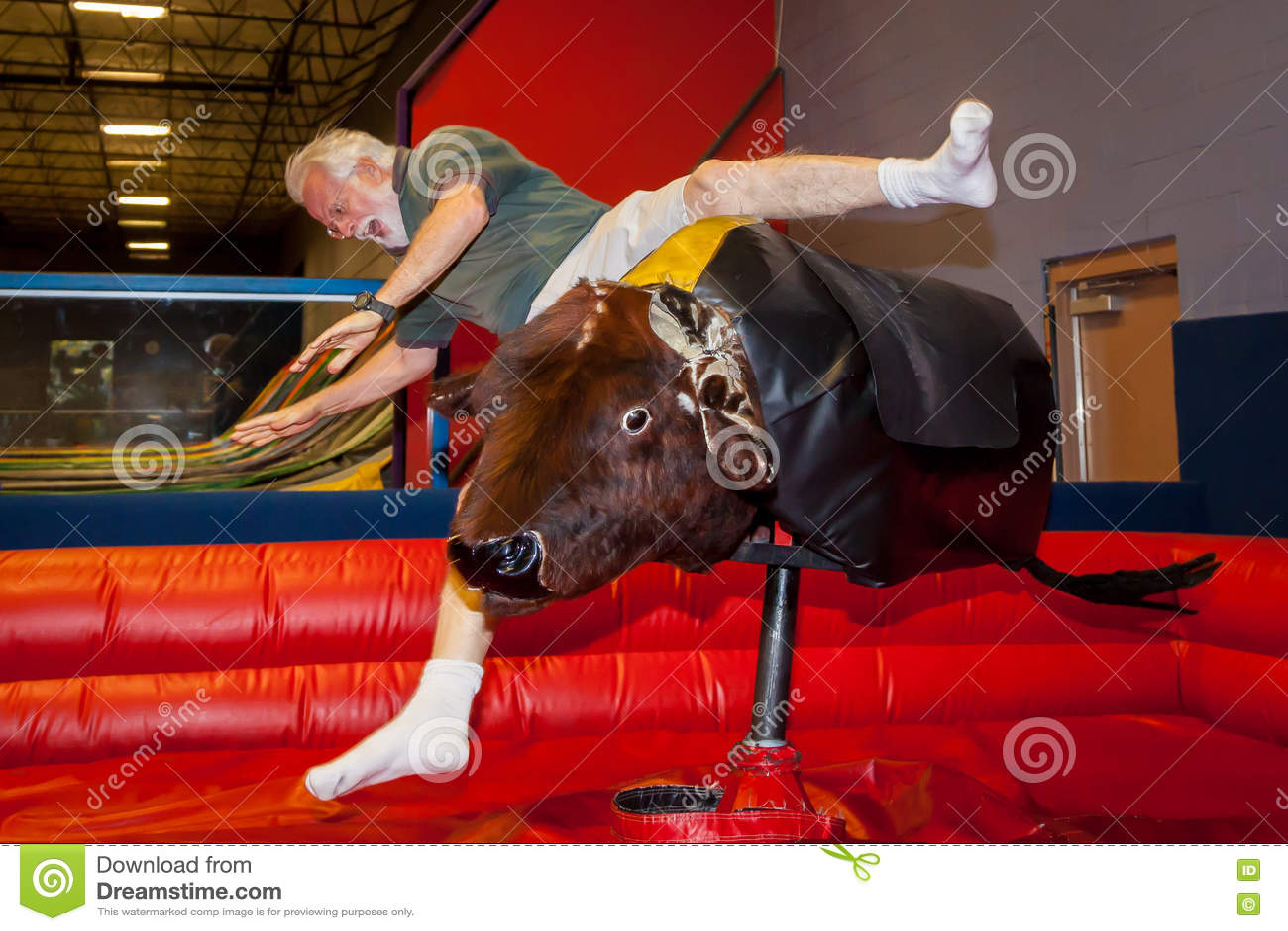 senior man falls off mechanical bull stock image