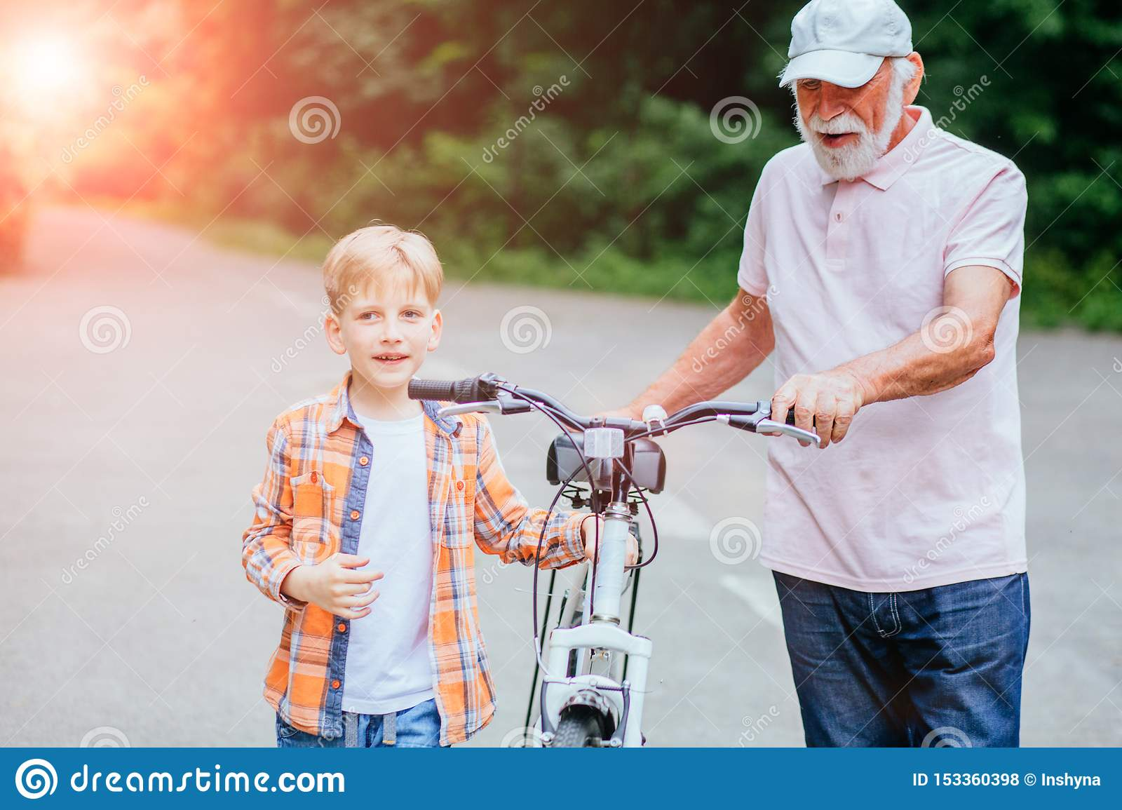 Senior man grandfather and grandson talking while walking with bicycle in the park. Family, generation, safety and people concept