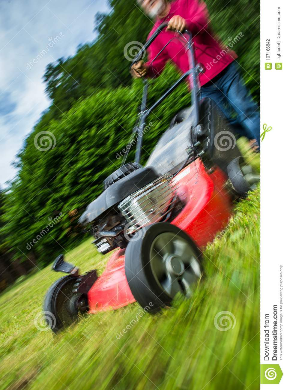 Senior Man Mowing The Lawn In His Garden Stock Photo