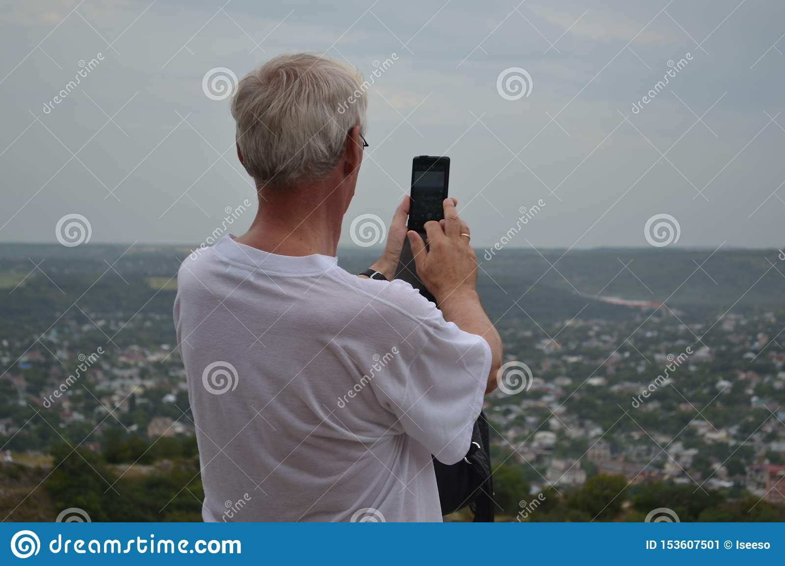 Senior man photographs on the phone a view of the city. Pyatigorsk, Russia