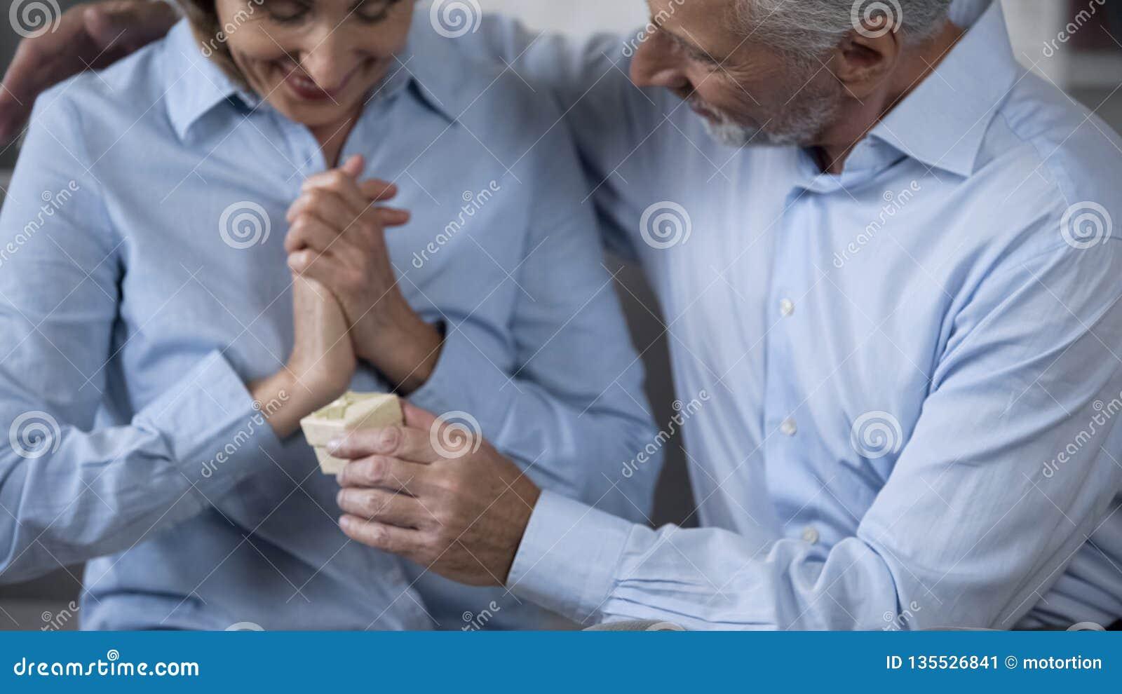 Senior man presenting gift to happy surprised wife, celebrating anniversary