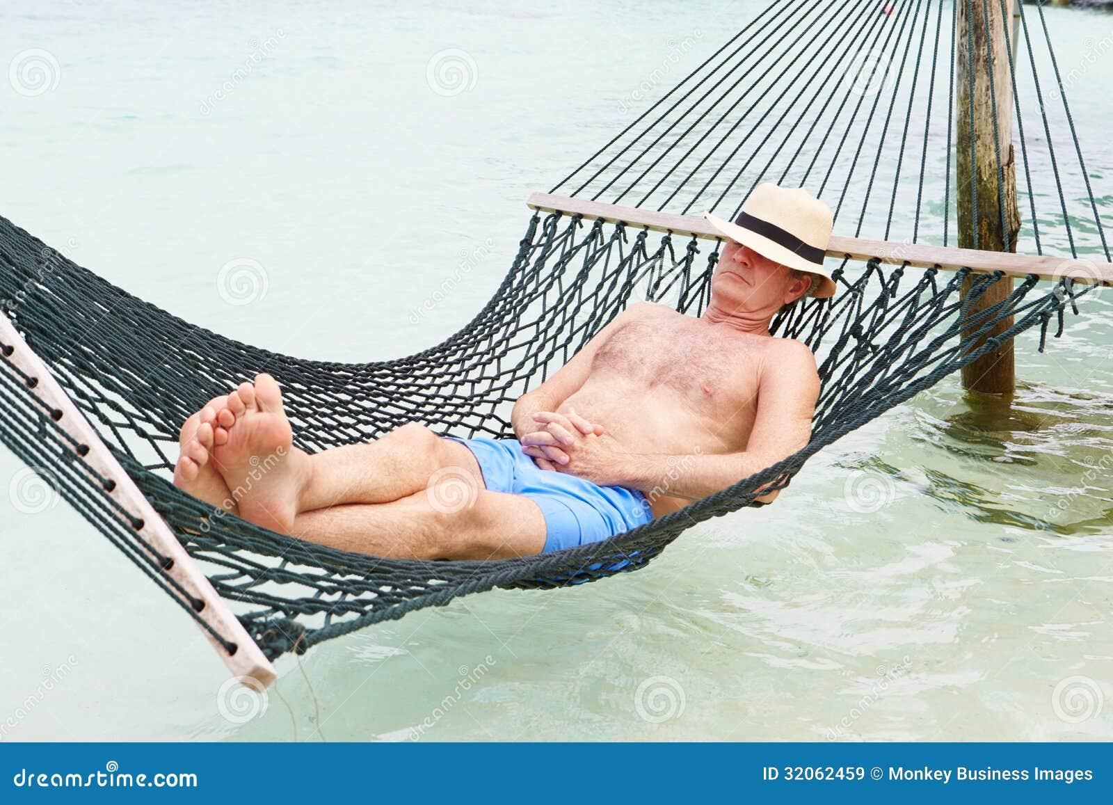 Moderaterna fortsätter att slå mot svaga grupper. - Sida 2 Senior-man-relaxing-beach-hammock-asleep-32062459