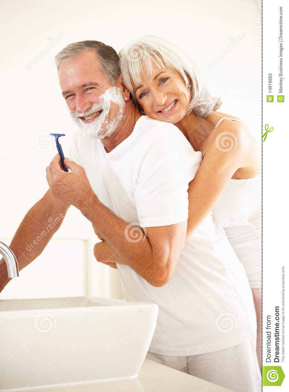 Senior Man Shaving In Bathroom Mirror With Wife Stock Photos Image