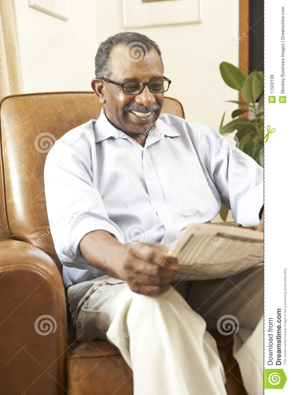 Senior man sitting in armchair reading newspaper royalty for Sitting in armchair