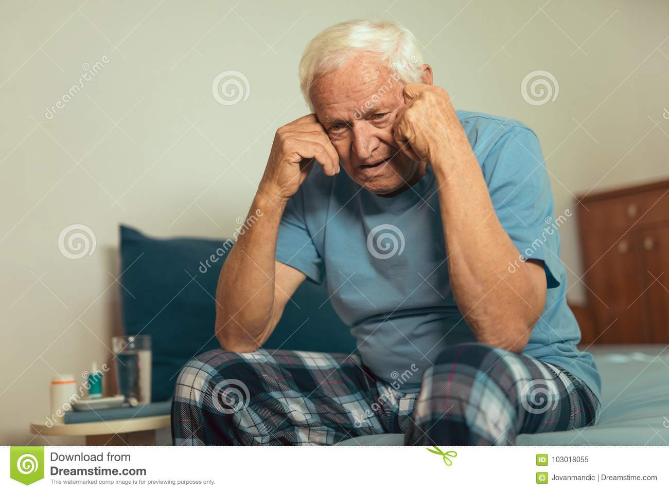 Senior Man Sitting On Bed Suffering From Depression