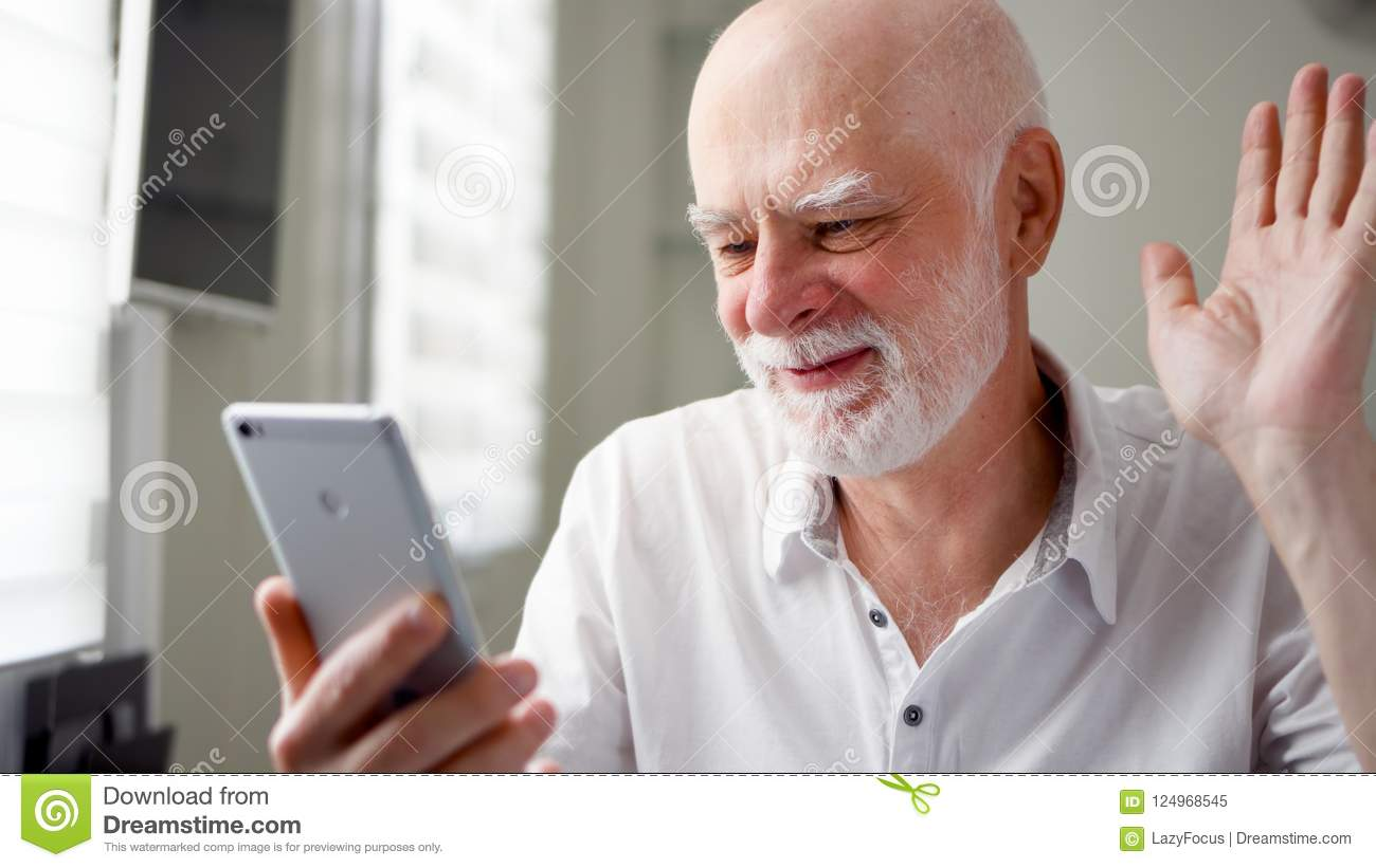 Senior man sitting at home with smartphone. Using mobile talking via messenger app. Smiling waving hand in greeting
