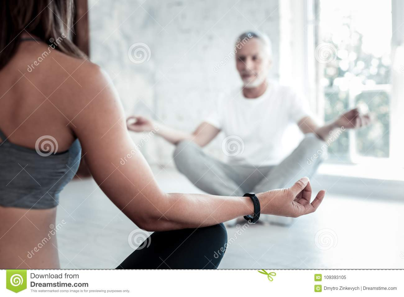 Selective focus on a young lady teaching mature men yoga while both sitting  on their mats and meditating in a yoga class.