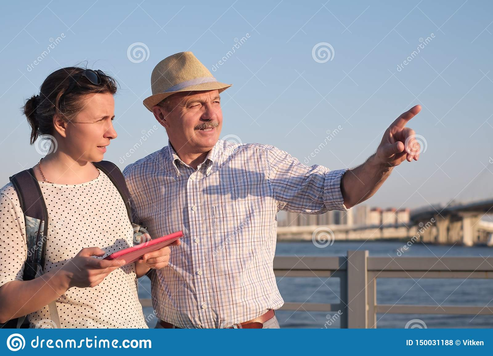 Senior man in summer hat shows the way on the map to young woman.