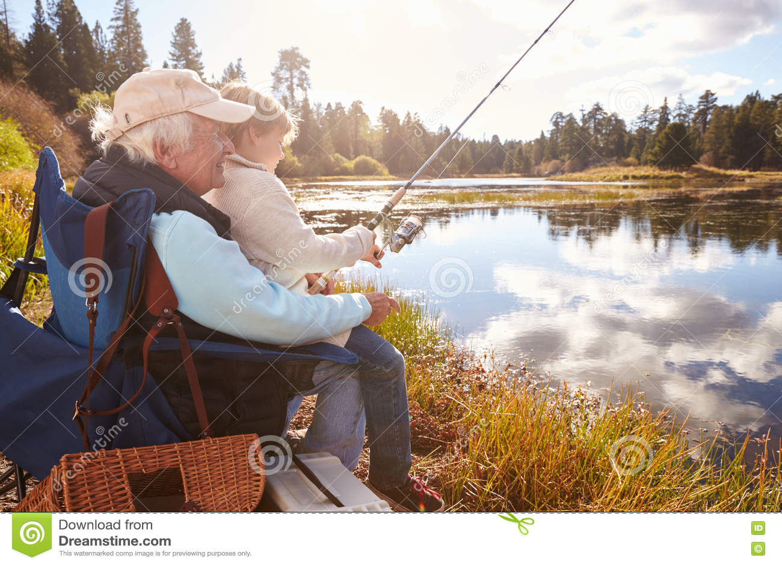 Senior man teaching his grandson to fish at a lake stock for Senior fishing license