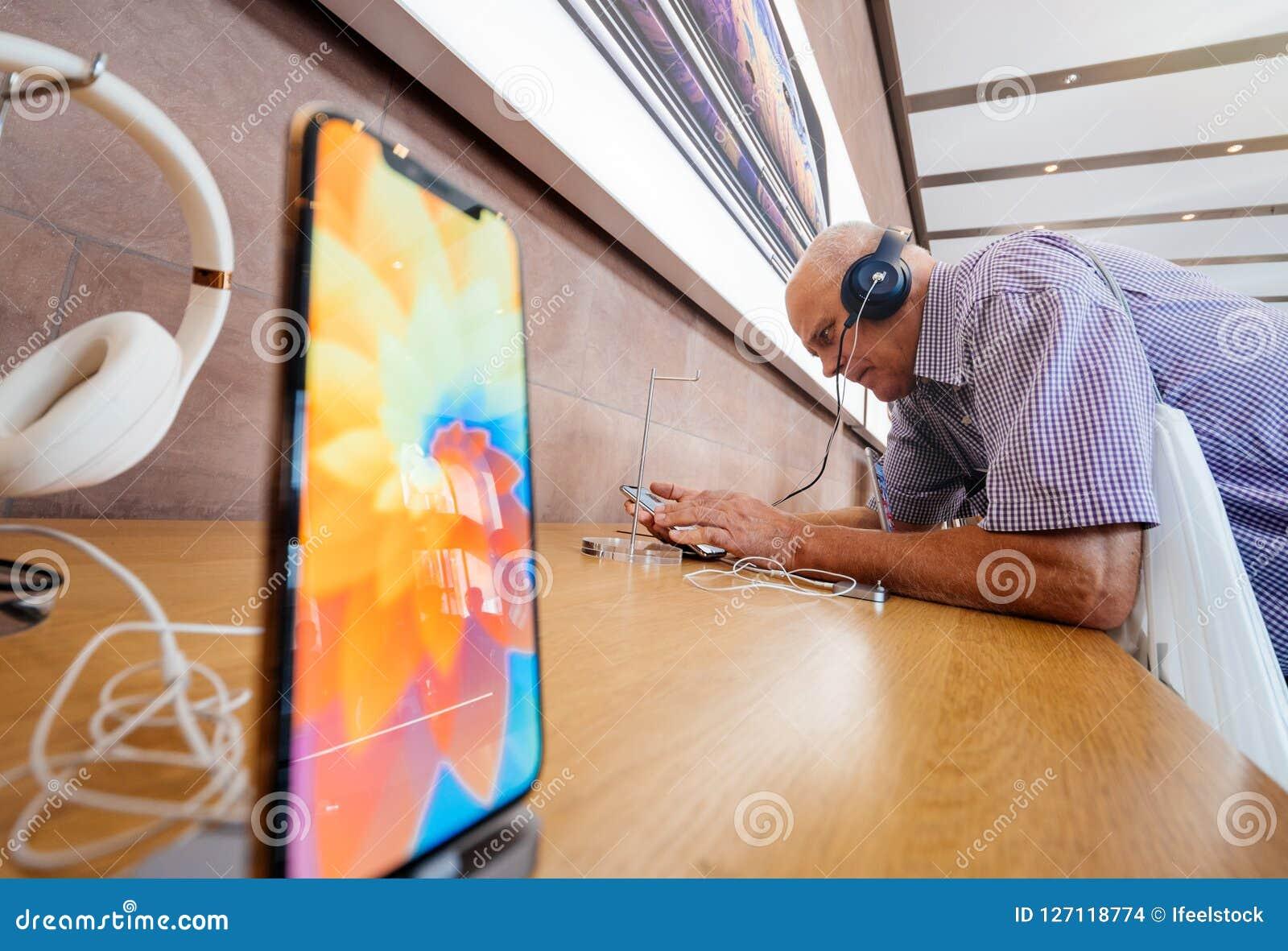 Senior Man Testing Headphones Beats In Apple Store Side View ... 80c32b8f2