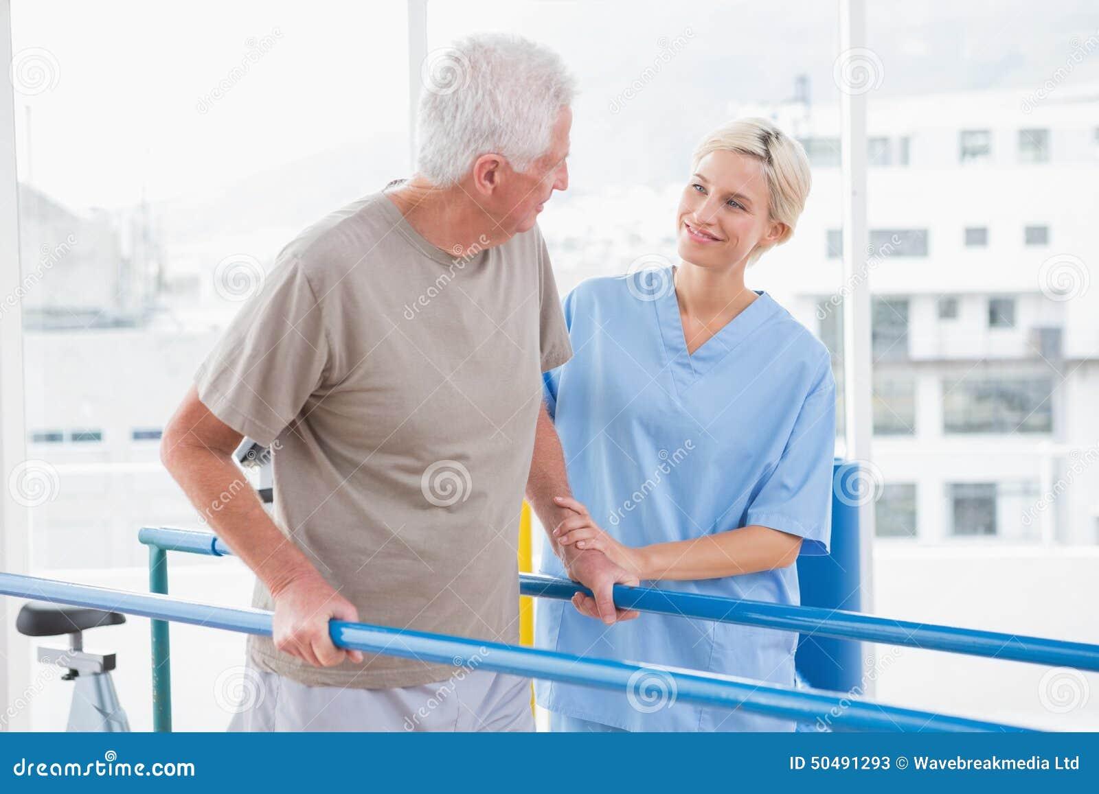 Senior man walking with therapist help