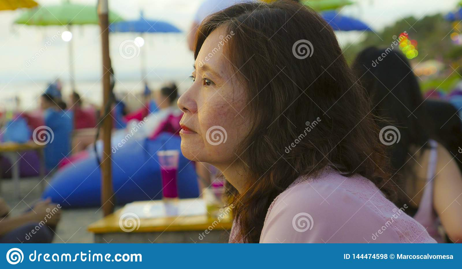 Senior mature Asian Chinese woman in her 50s or 60s looking relaxed and thoughtful sitting at tropical beach resort in Summer