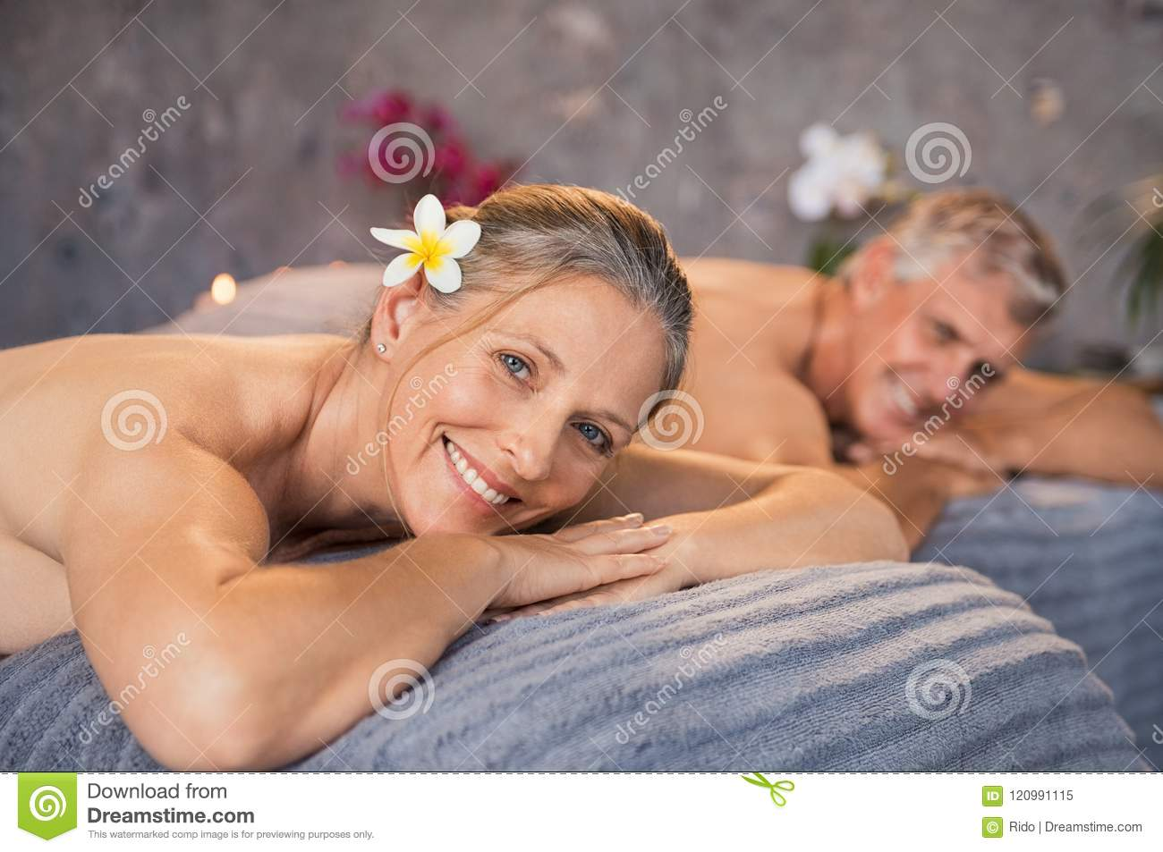 Senior men and beautiful women lying down on massage beds at spa. Mature  couple lying on massage table and smiling while looking at camera.