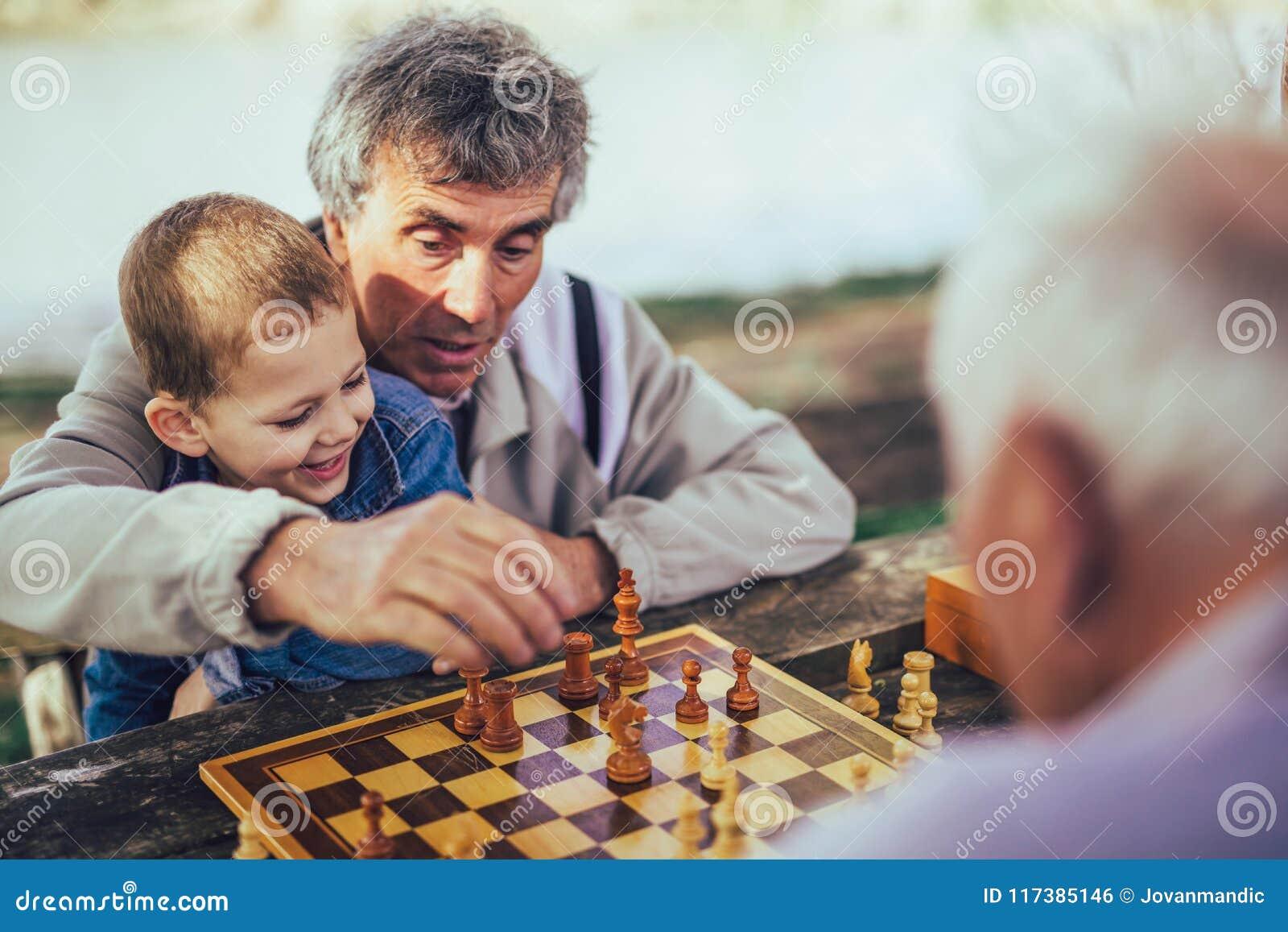 Senior men having fun and playing chess at park