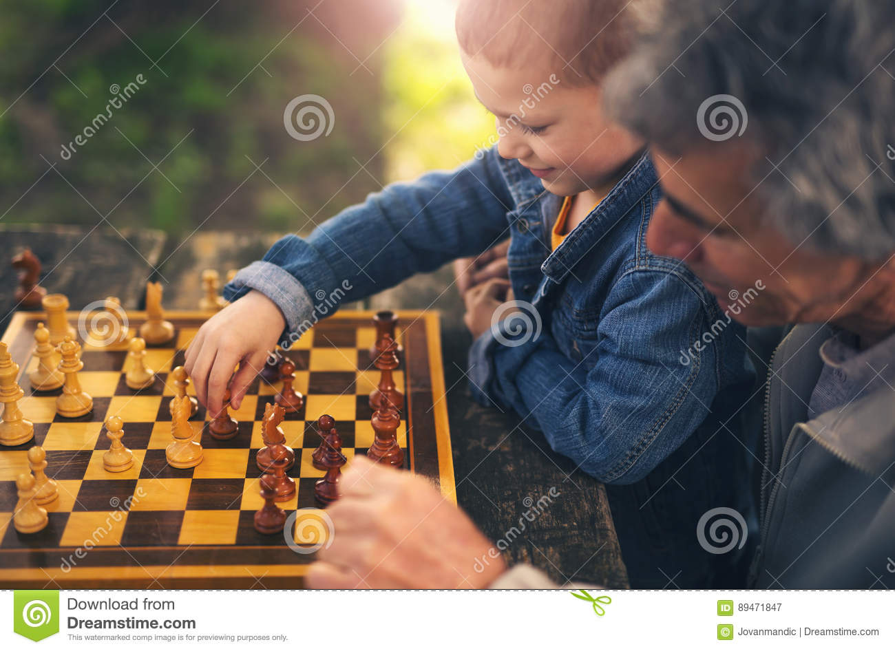 Senior men having fun and playing chess at park, spend time with grandson