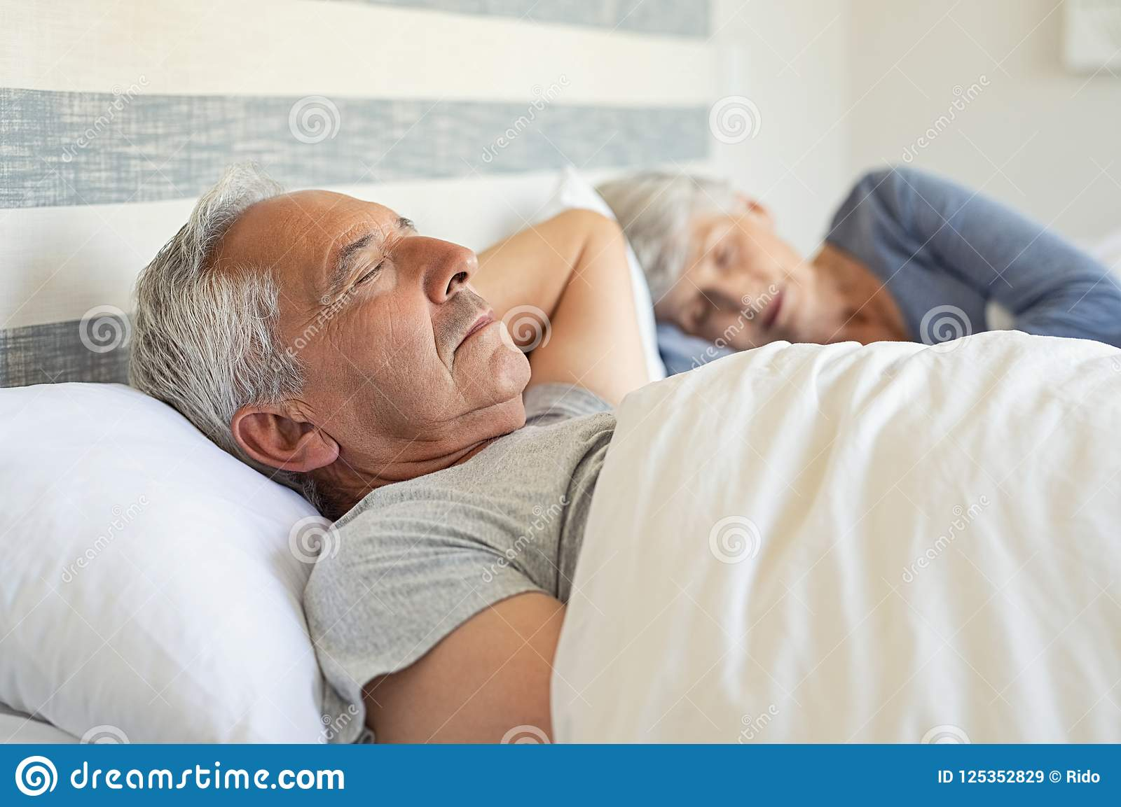 Mature couple resting with eyes closed during the morning. Old husband and  wife sleeping together in their bed with peace.