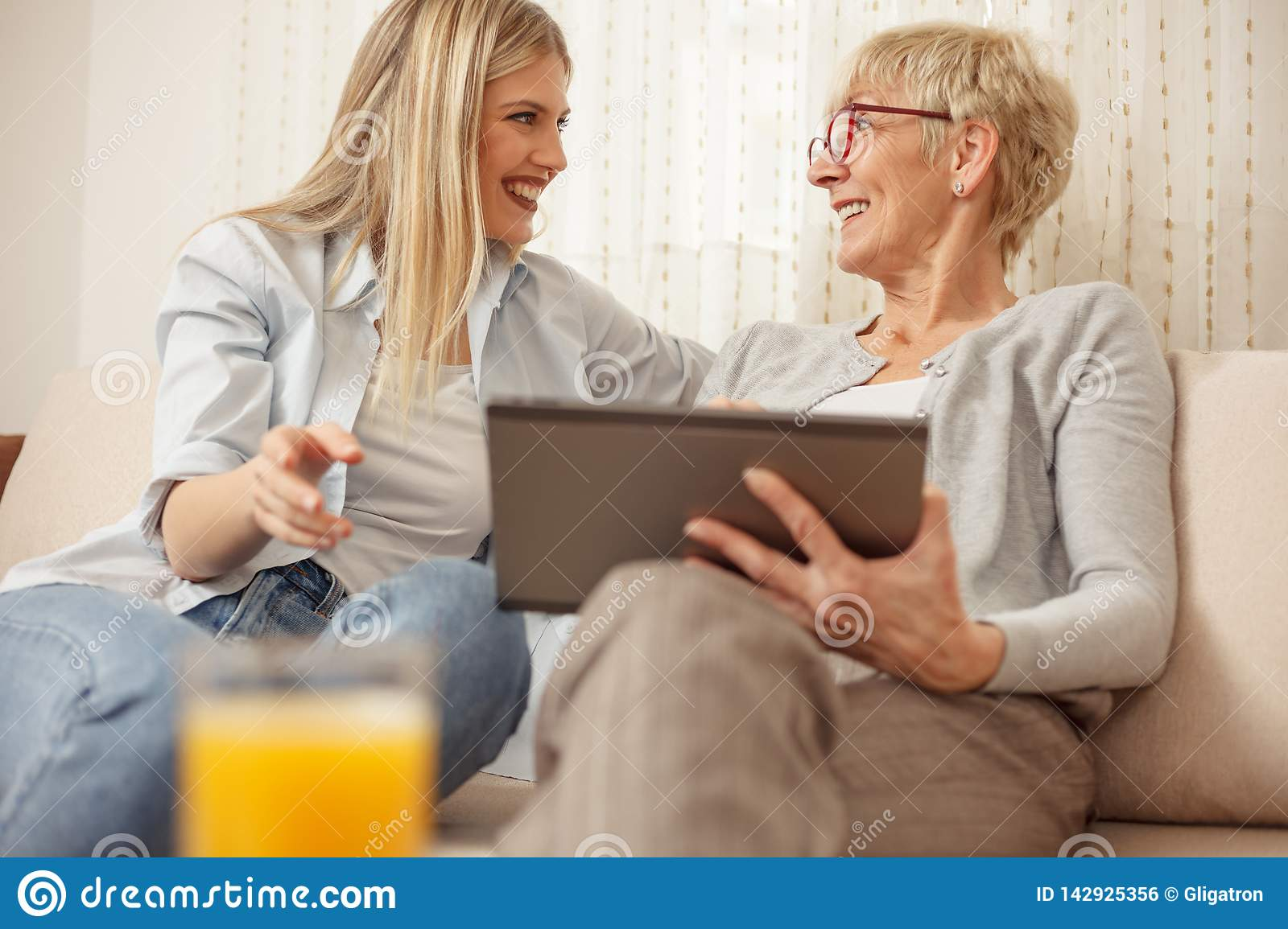 Mother and daughter laughing and looking at each other while using a tablet