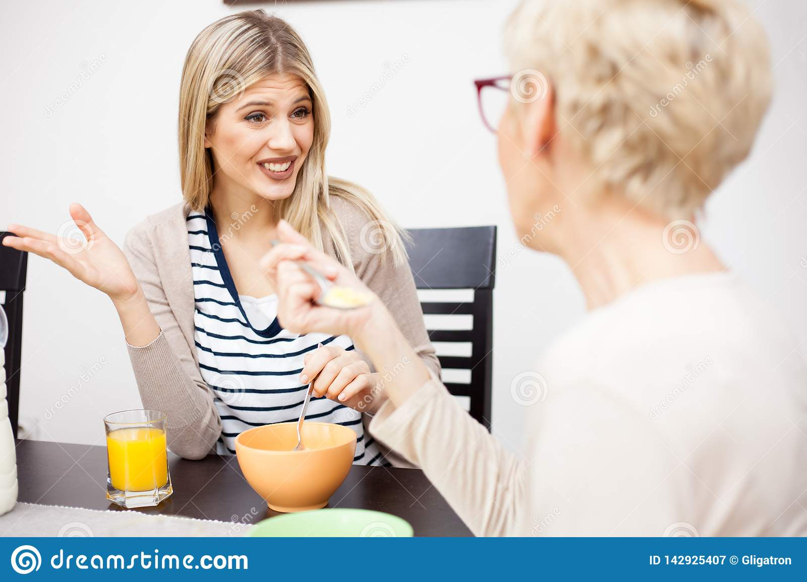 Young daughter and her senior mother eating healthy breakfast and talking