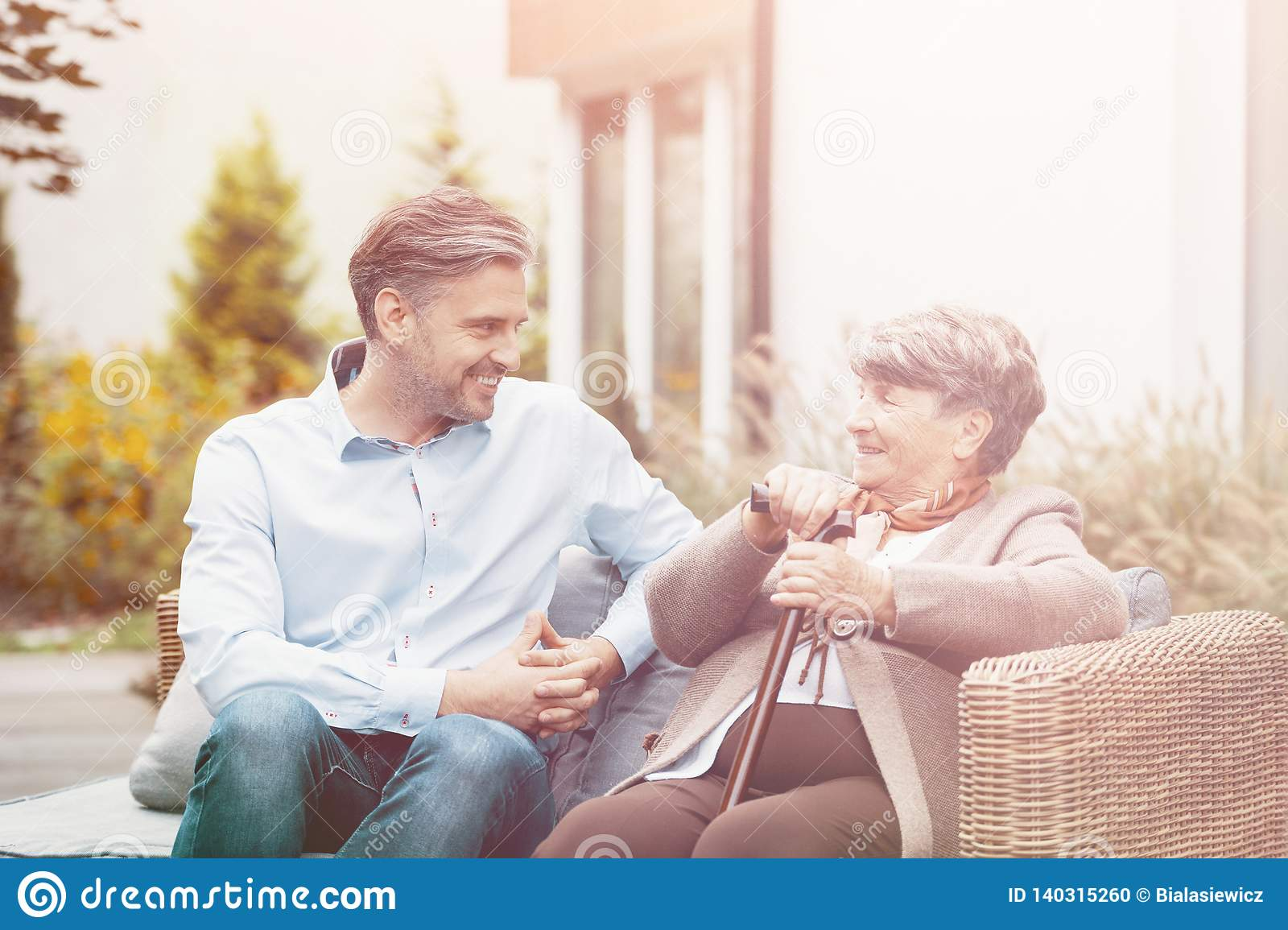 Senior mother and son talking while sitting on a wicker sofa outdoor
