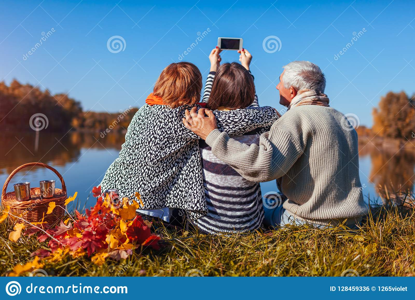 Senior parents taking selfie by autumn lake with their adult daughter. Family values. People having picnic