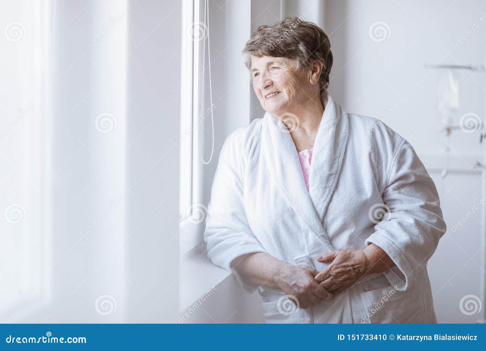 Senior popielata dama jest ubranym bia?ego bathrobe stoi bezczynnie okno przy karmi?cym domem