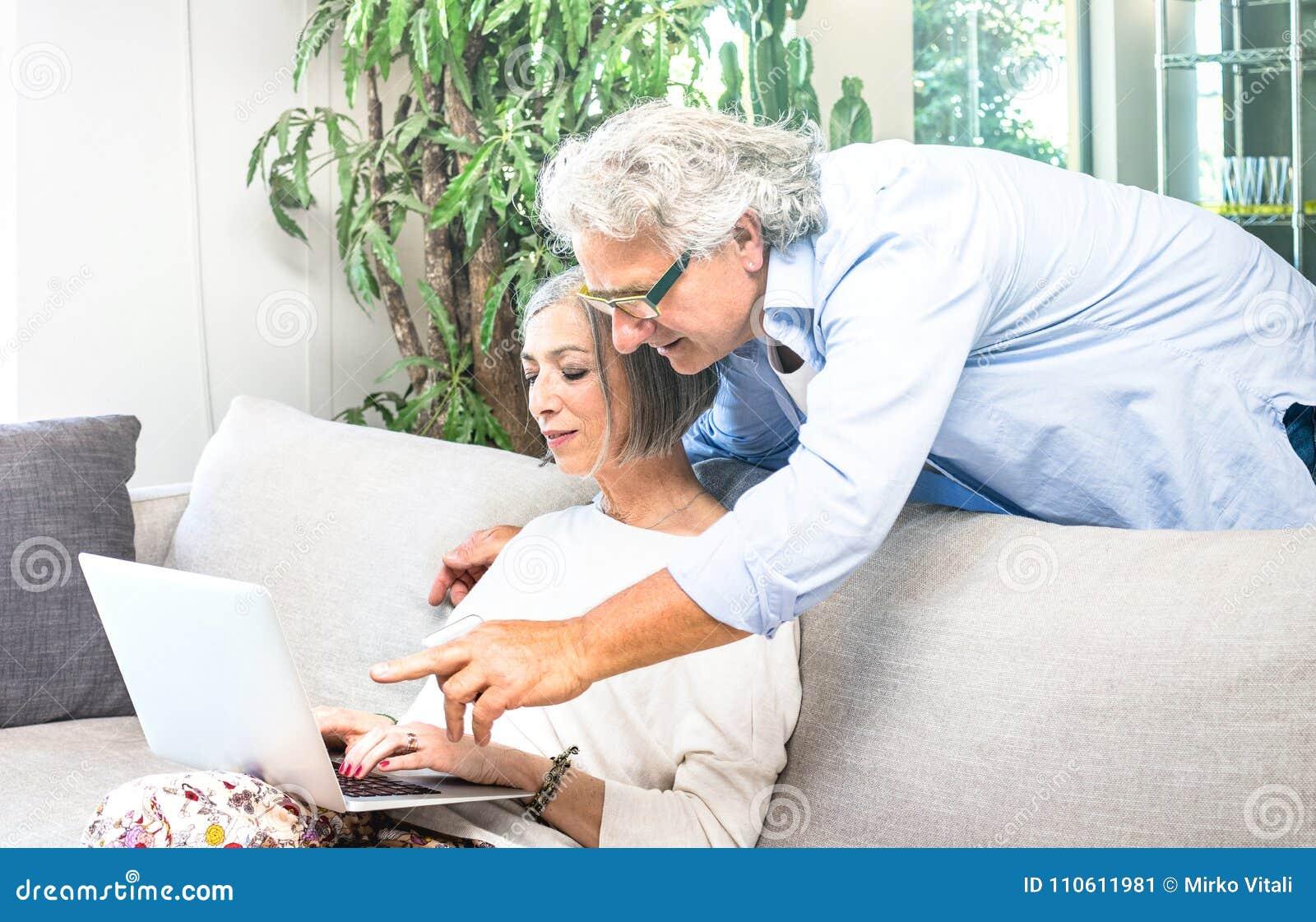 Senior przechodzić na emeryturę pary używa laptop na kanapie w domu - El