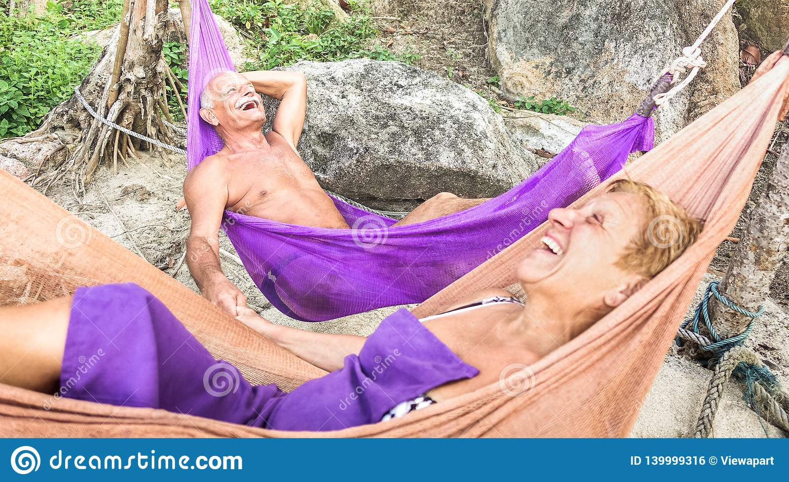 Senior retired couple vacationer relaxing on hammock at beach - Active youthful elderly and happy travel concept on tour around