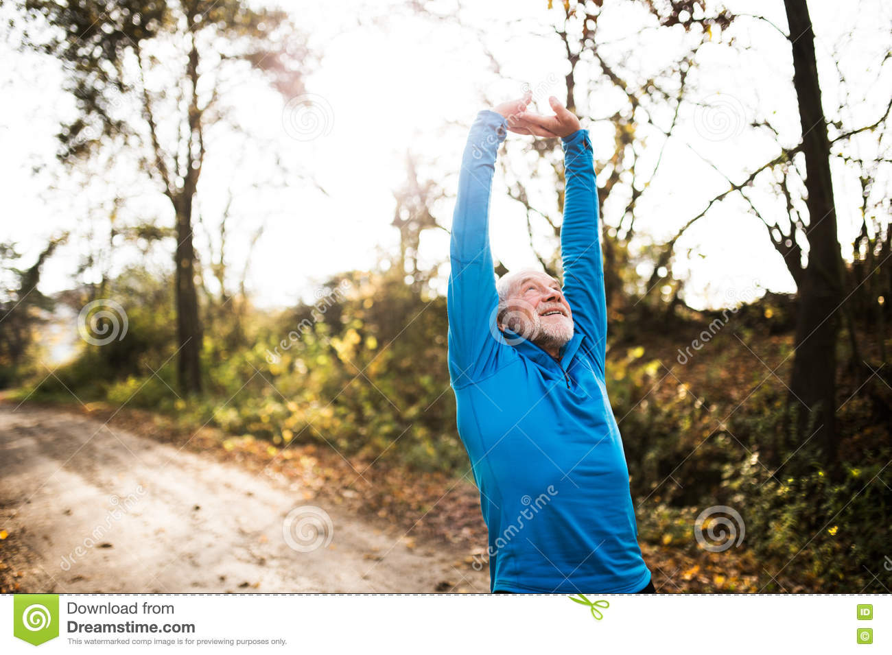 Senior runner doing stretching in sunny autumn nature.