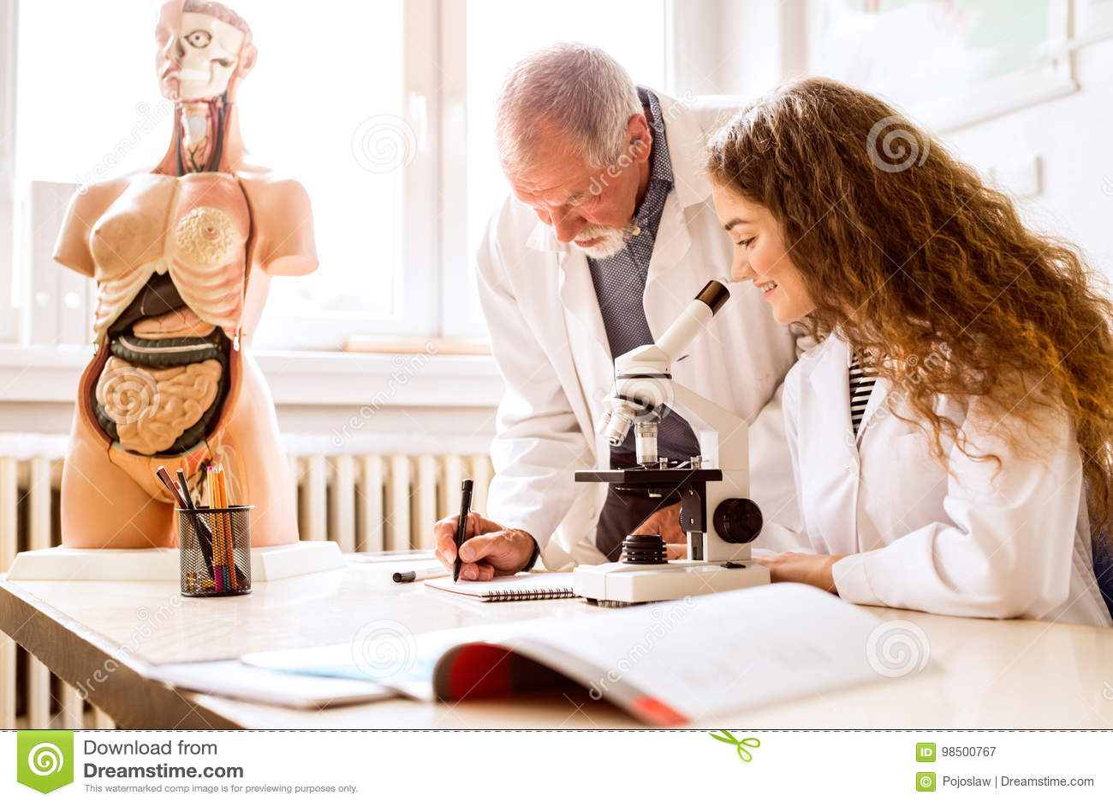 Senior Teacher Teaching Biology To High School Student In Labora