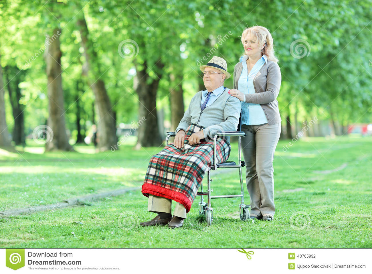 Senior in wheelchair sitting in park with his wife