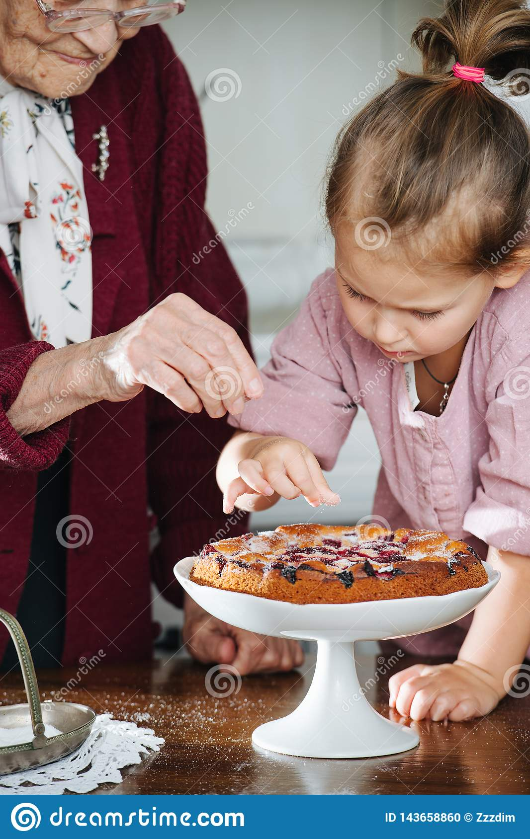 Senior woman along with her granddaughter pouring powdered sugar on tasty pie