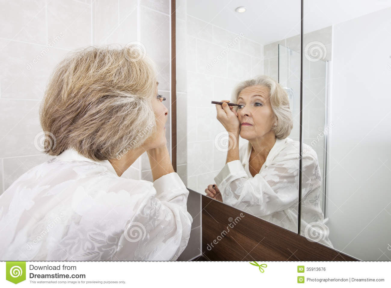 Senior woman applying eyeliner while looking at mirror in for Looking for mirrors