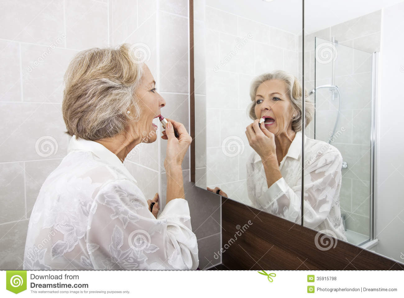 Senior woman applying lipstick while looking at mirror in for Looking mirror