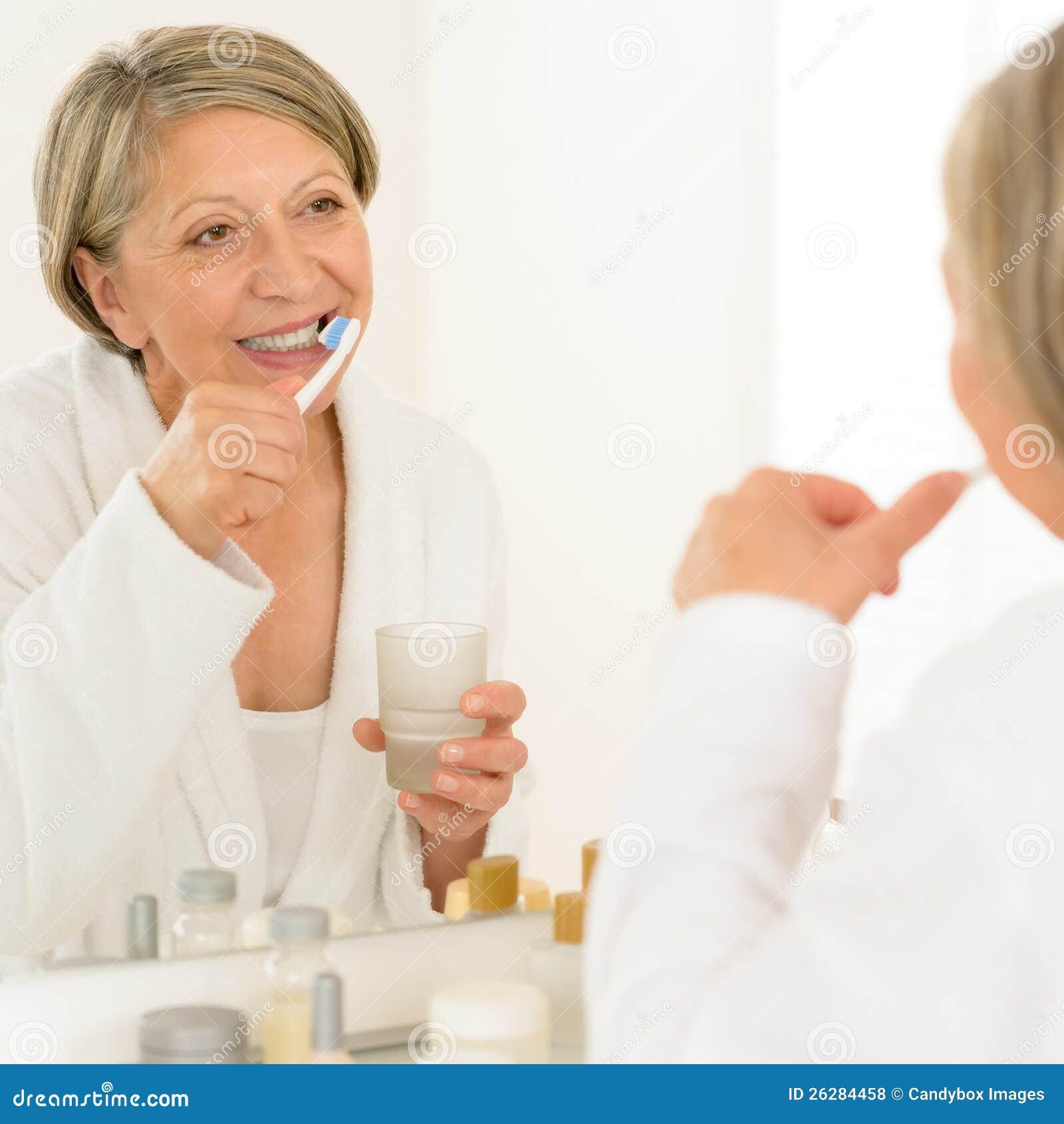 Senior woman brushing teeth bathroom mirror