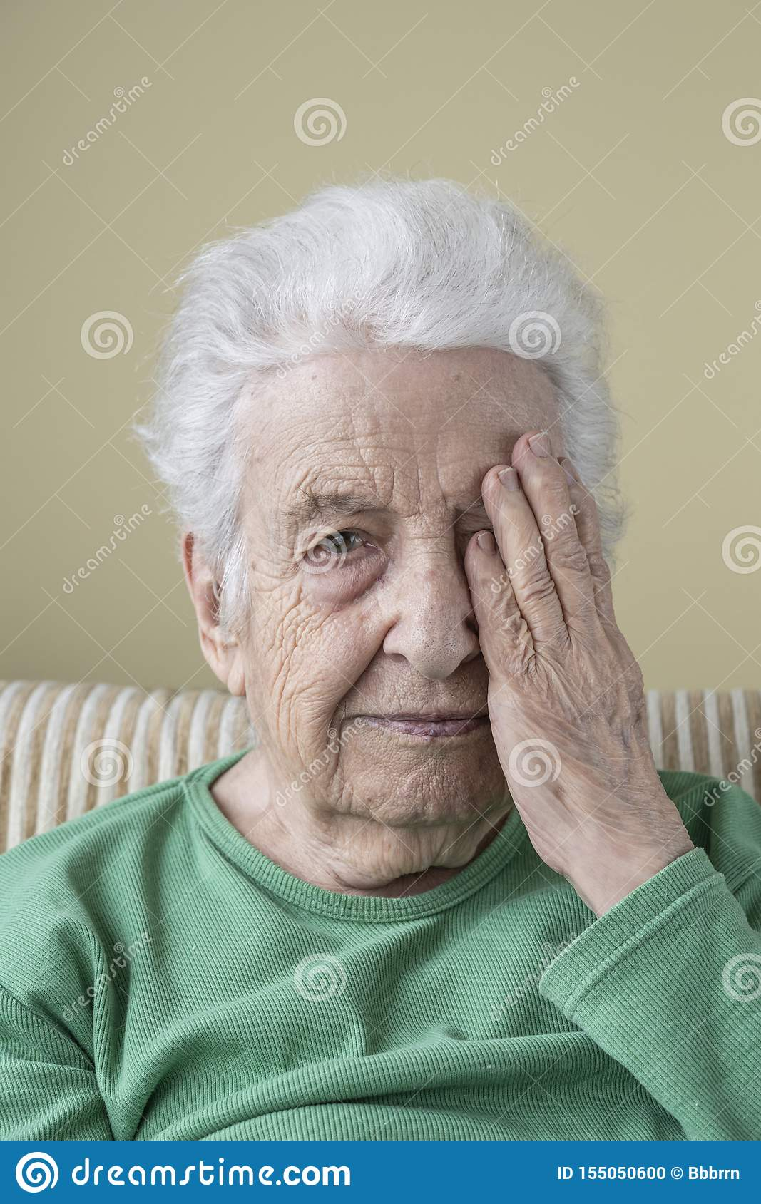 Senior woman closing her one eye with her hand