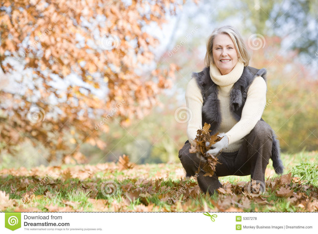 Senior woman collecting leaves on walk