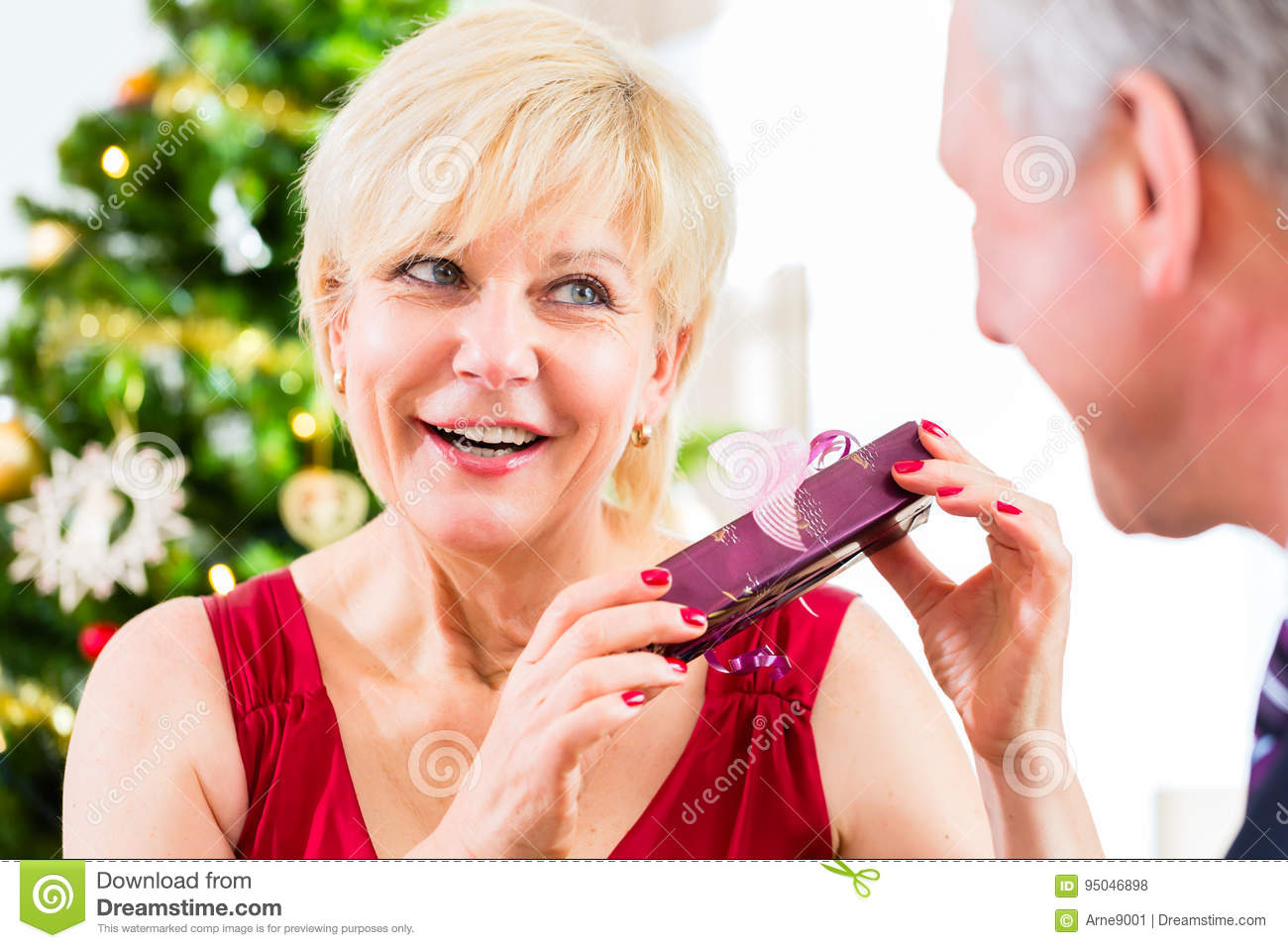 Senior Woman Is Curious About Christmas Gift Stock Photo - Image of ...