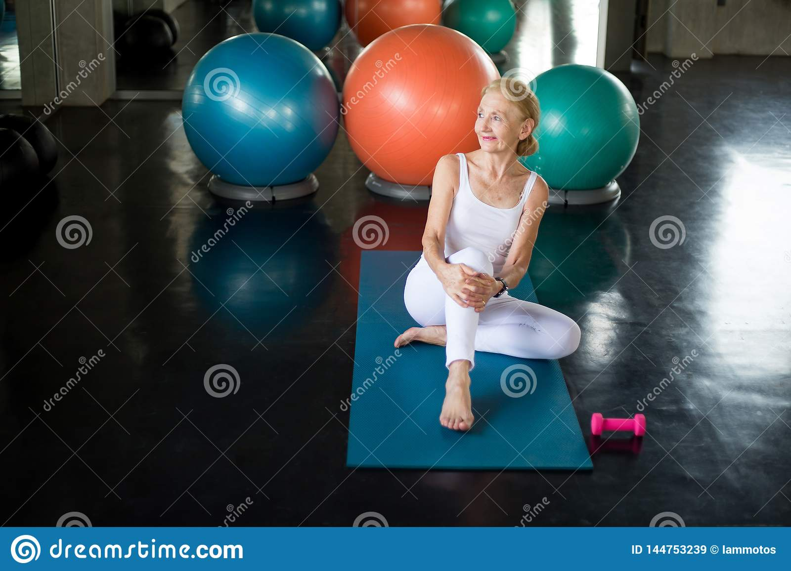 Senior woman Doing yoga in fitness gym. aged lady exercising. Old female taking a break from workout .Mature sport training.