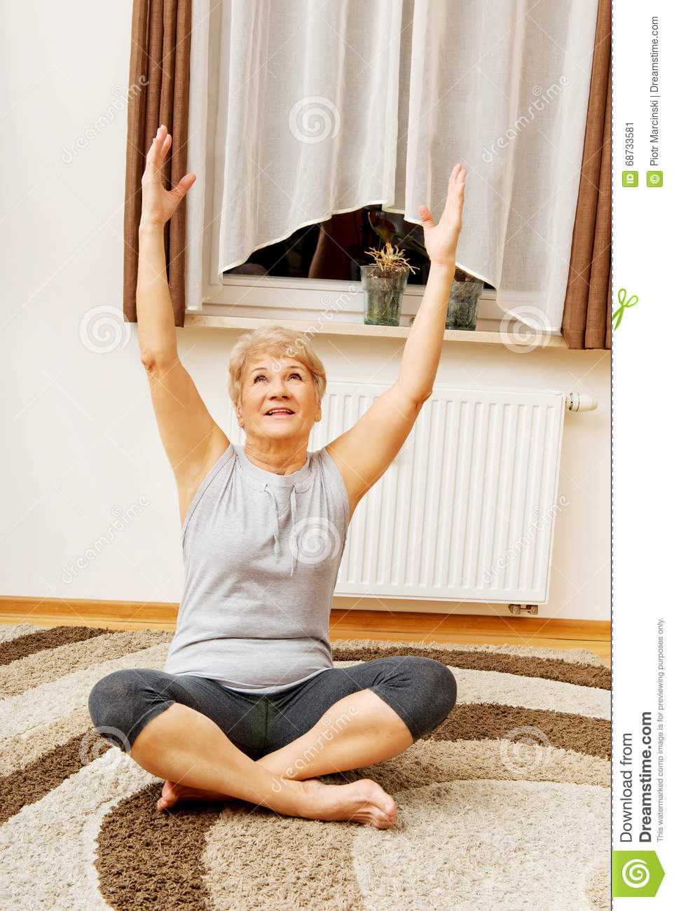 Senior woman doing yoga in living room stock photo image for Living room yoga sessions