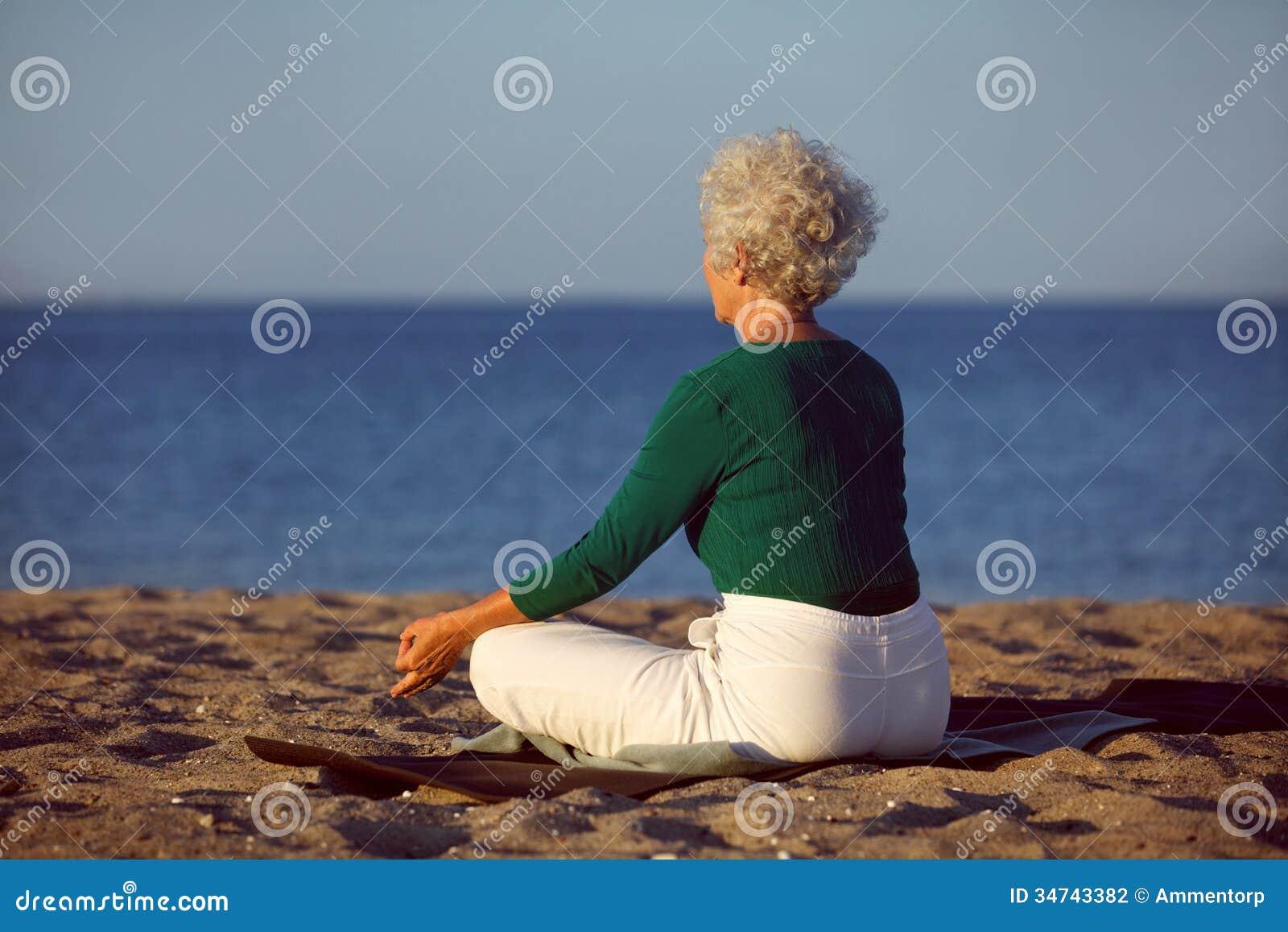 Senior Woman Doing Yoga Meditation On Beach Stock