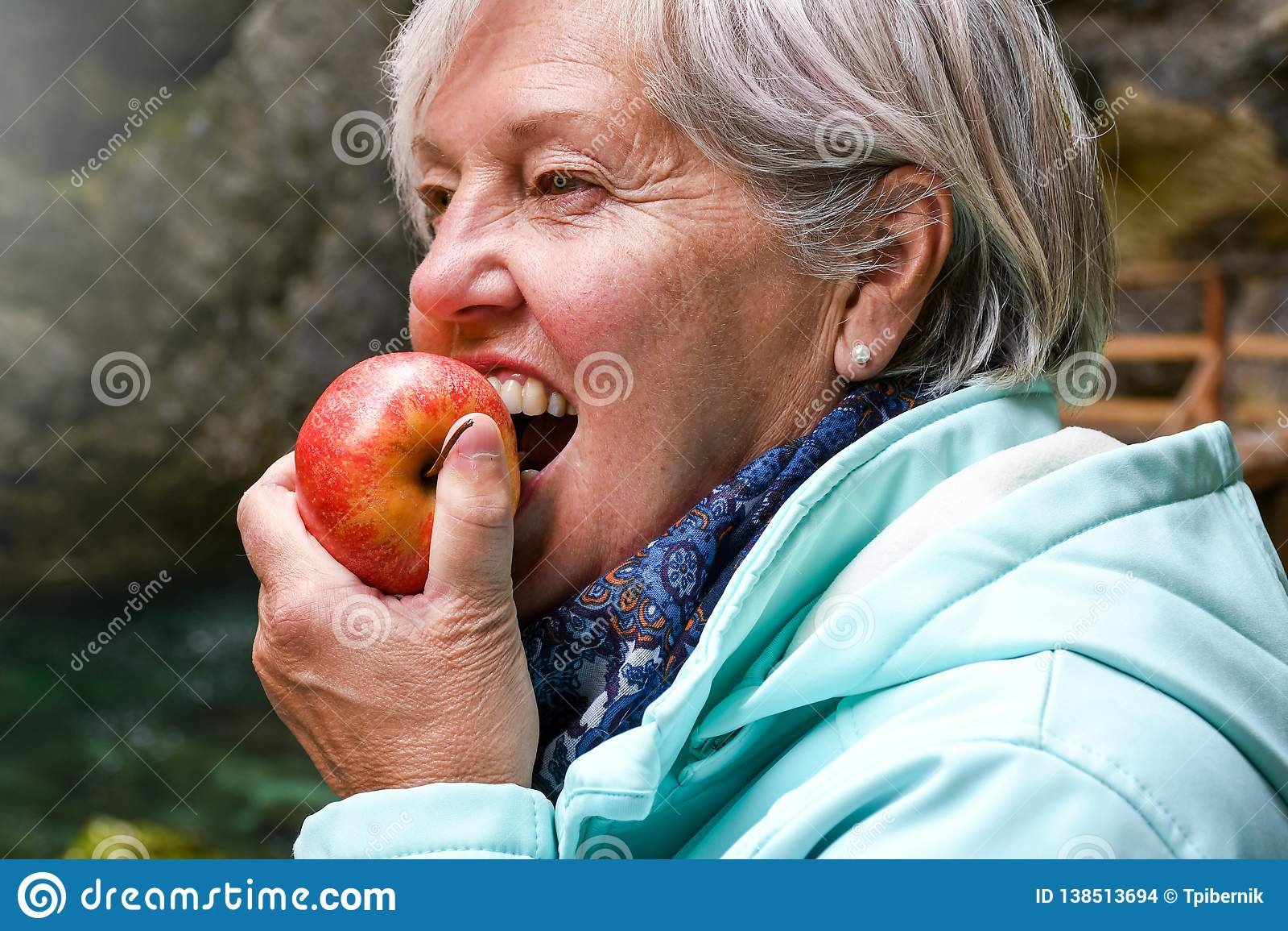 Senior woman eating apple outside in the park
