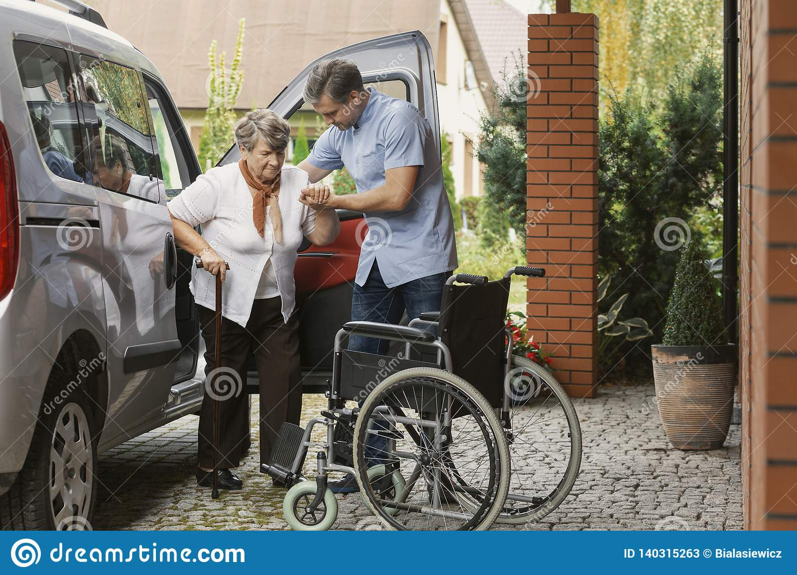Senior woman getting out of the car with the help of a nurse