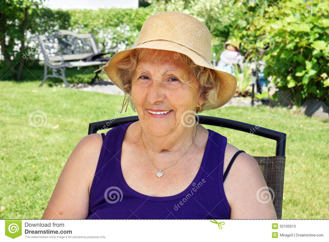 Senior woman with straw hat in the shade enjoying summer